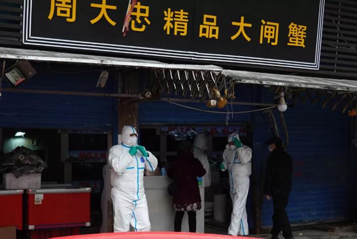 防疫工作人员对华南海鲜市场进行检查。图片来自新京报