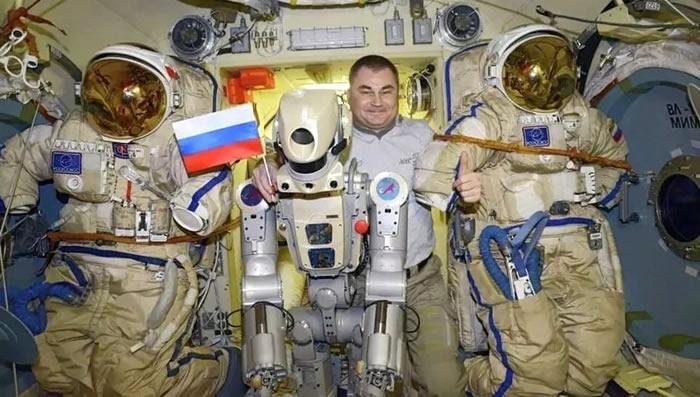 俄罗斯宇航员亚历山大·斯科沃佐夫在国际空间站教人形机器人费奥多尔用毛巾擦汗