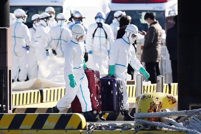 身着防护装备的卫生官员从停泊在日本横滨的钻石公主号游轮上带出行李箱,大众普遍认为这些行李箱的主人,就是验出冠状病毒阳性后从船上撤离送医的乘客。 PHOTOGRA