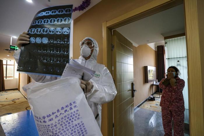 这张摄于2020年2月3日的照片显示,一名医生正在检查一张肺部的计算机断层扫描影像,当时他在武汉隔离区的一间病房巡视。 武汉位于中国湖北省中部,是新型冠状病毒疫