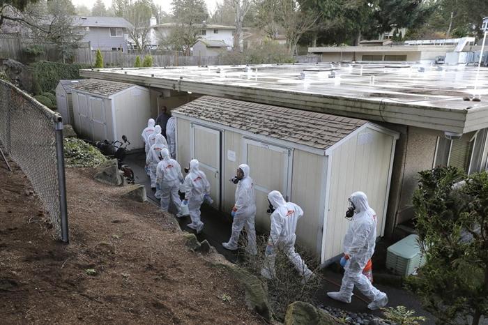 2020年3月11日星期三,Servpro灾后重整公司的工作人员身穿防护装和防毒面具,走进位于美国华盛顿州科克兰(Kirkland)的生命照护中心(Life C