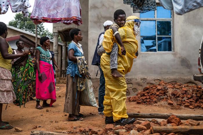 去年在贝尼,一名医护人员背着14岁的卡库莱. 卡文迪瓦(Kakule Kavendivwa)走向一辆停在路边的救护车。 卡库莱的姊妹在前一天曾带他去附近的卫生中