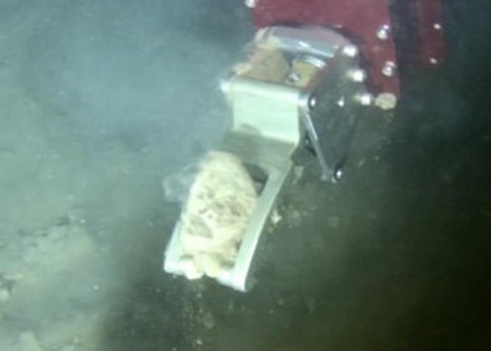 潜水器以机械手在深渊海底取样。