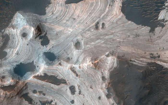 这张照片是由美国宇航局火星勘测轨道飞行器(MRO)机载高分辨率科学实验成像相机(HiRISE)拍摄的,呈现出直径140公里的霍尔顿陨坑中存在漩涡层状砂岩。