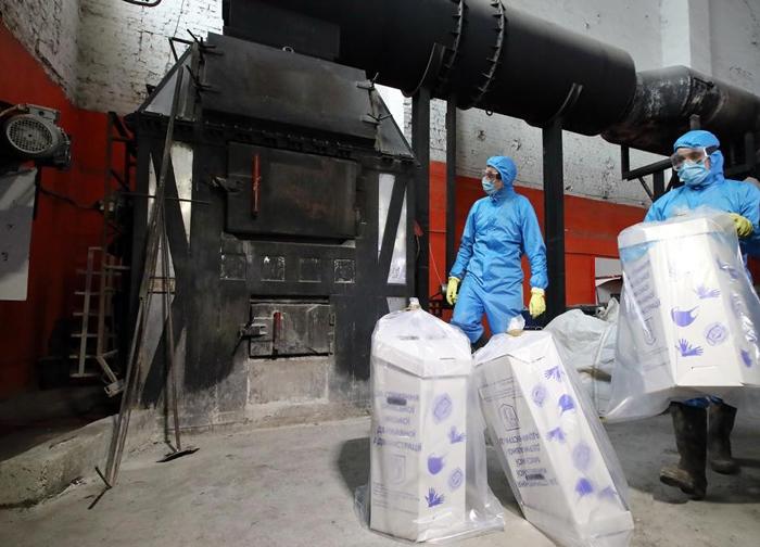 乌克兰基辅的工人将用过的医疗口罩和手套丢进焚化炉烧掉。 PHOTOGRAPH BY VOLODYMYR TARASOV, UKRINFORM/BARCROFT