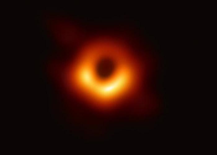 """首张黑洞图中,明亮的橙色背景下可见黑洞的""""影子""""。"""