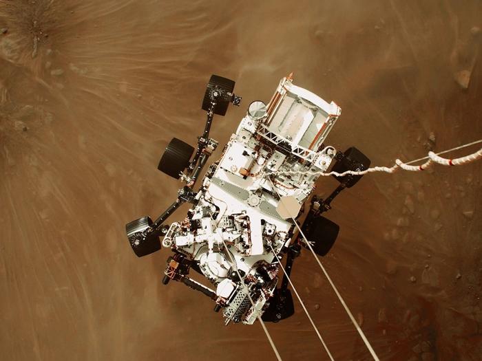 利用「空中吊车」协助探测车着陆──机载相机拍摄了毅力号探测车成功登陆火星的影像和影片,此时的探测车以电缆与空中吊车相连,再数公尺就要轻触火星地表。 PHOTO