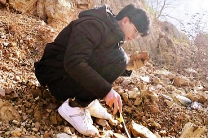 刘一龙在野外采集化石。(通讯员 王紫璇 摄)
